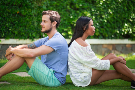 lovers quarrel: Multi-ethnic Couple Sitting Back to Back on Grass