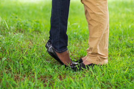 Woman standing on boyfriends toes in park