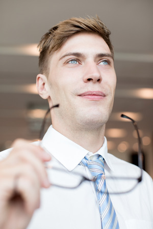 Closeup of Content Business Man Taking off Glasses