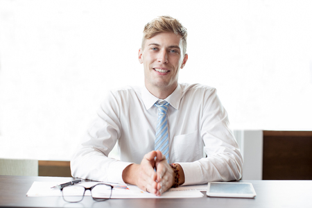 Smiling Business Man Sitting at Office Desk