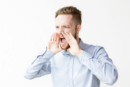 loud: Serious Young Attractive Man Shouting Loud Stock Photo