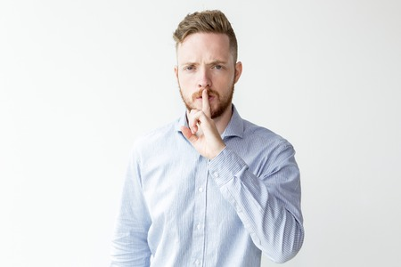 Serious Young Man Showing Silence Gesture
