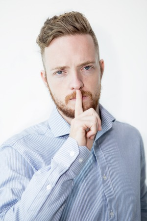 Serious Young Man Making Silence Gesture