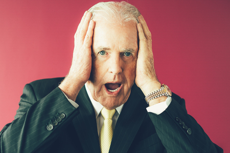 Closeup portrait of shocked senior business man clutching head with his mouth open. Isolated front view on purple background.