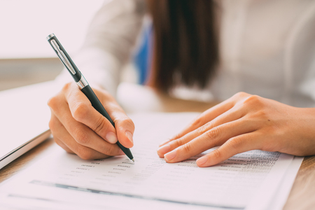 Hand of businesswoman or accountant checking financial document with ballpoint pen at table in office