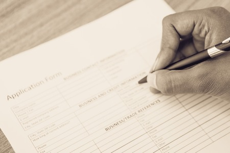 Close-up of hand of female candidate filling application form with ballpoint pen sitting at desk Stock Photo