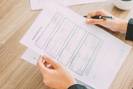 Jonge Aziatische zakenvrouw of HR-manager aan tafel zitten in office, sollicitatieformulier van kandidaat te houden en het te lezen Stockfoto