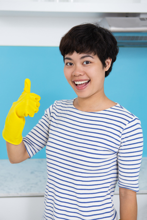 Happy Asian Housewife Showing Thumb Up in Kitchen