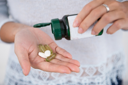 Cropped View of Woman Pouring Pills From Bottle