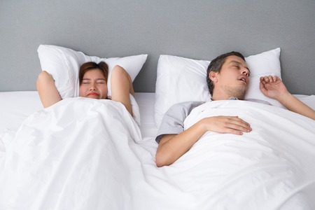 Angry Asian woman annoyed with husbands snoring Stock Photo