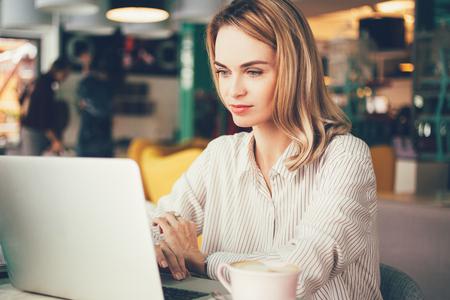 Geconcentreerde vrouwelijke freelancer in co-werkruimte