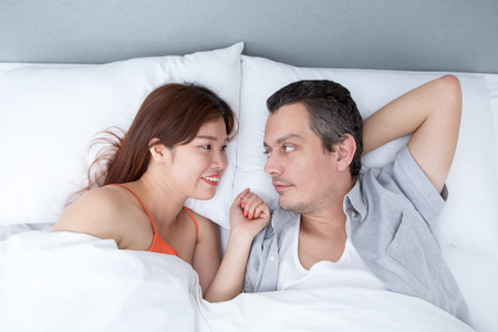 bedroom: Smiling Couple Chatting and Lying in Bed Stock Photo
