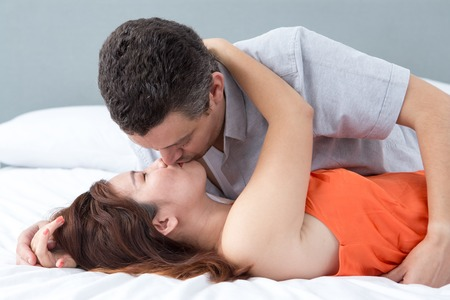 bedroom: Passionate Couple Embracing and Kissing in Bed