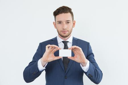 深刻な自信を持っている青年実業家表示カード 写真素材