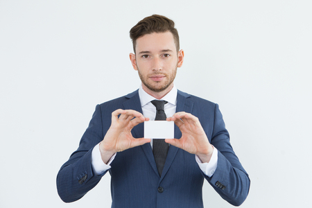 Serious confident young businessman showing card Stok Fotoğraf