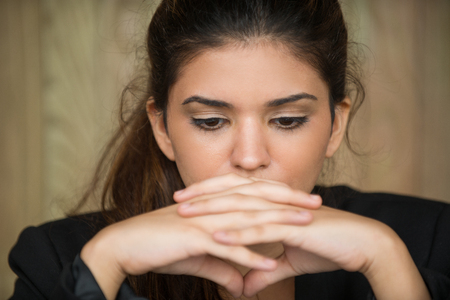 Close-up of young businesswoman in deep thought