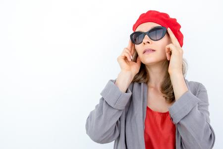 Enigmatic pensive woman adjusting sunglasses