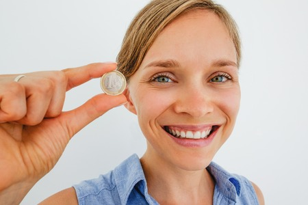 Closeup of Smiling Woman Holding One Euro Coin Stockfoto