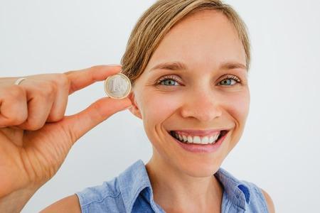 Closeup of Smiling Woman Holding One Euro Coin Archivio Fotografico
