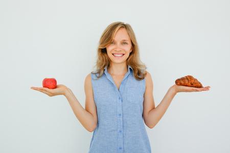 Sonriendo hermosa mujer con manzana y croissant Foto de archivo