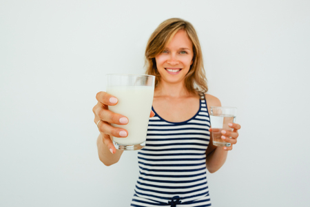 extending: Smiling Pretty Woman Offering Glass of Milk Stock Photo