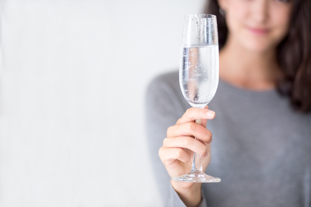 cheer full: Close-up of champagne flute in hand of young girl Stock Photo