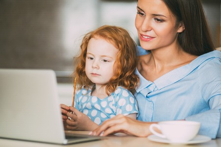 Smiling mother sitting at laptop with little girl