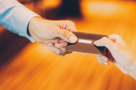 Man geeft creditcard aan kassier voor betaling