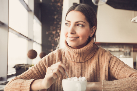 Dreamful woman drinking hot chocolate in cafe