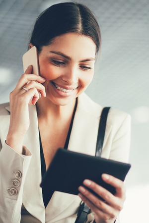 Mobile businesswoman using tablet and phone