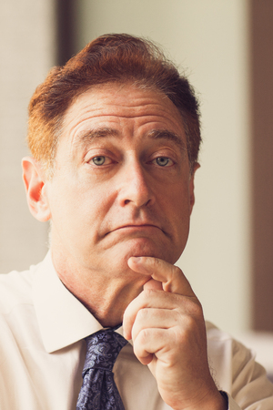 unsatisfied: Surprised mature businessman looking unsatisfied
