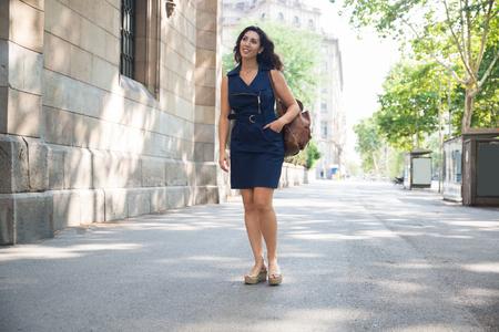 Gelukkige modieuze jonge vrouw die in stadsstraat loopt