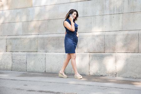 sidewalk talk: Serious woman walking along wall with cellphone Stock Photo