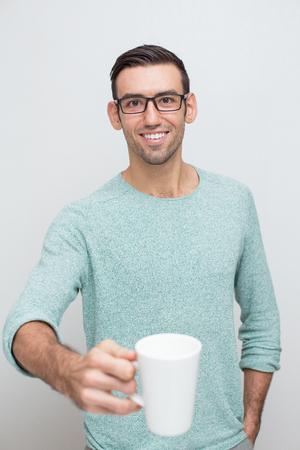 extending: Handsome Young Smiling Man Offering Mug of Tea