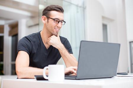 Glimlachende jonge knappe man aan het werk op laptop