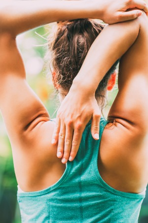 Rear view of woman stretching arms in park. She sliding one hand directly down middle of back and pushing arm with opposite arm. Triceps stretch concept