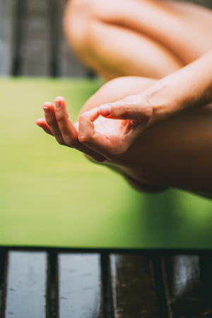 Woman in lotus position practicing mudra meditation. She holding hands into mudra by joining index finger and thumb on each hand. Unrecognizable woman facing up her palms. Relaxation exercise concept