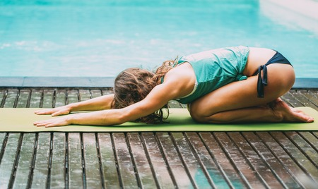 Young woman stretching near swimming pool. She dropping forehead to exercise mat and reaching hand on mat. She doing relaxation exercise. Morning stretching concept