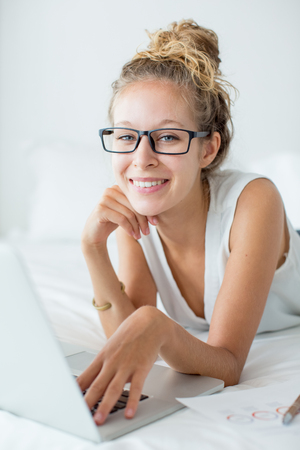 Smiling Woman Lying on Bed and Working on Laptop
