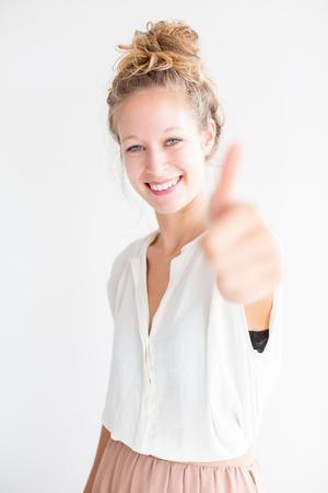 親指を現して若い素敵な女性の笑顔 写真素材