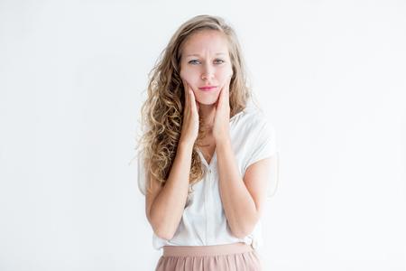 elasticidad: Preocupada mujer hermosa joven tocando mejillas
