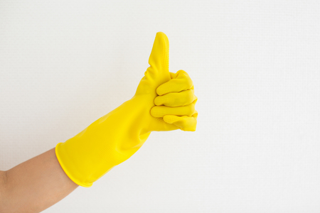 Close-up of hand in rubber glove showing thumb-up as symbol good job opposite white background. Woman approving dusting. Quality of clearness concept
