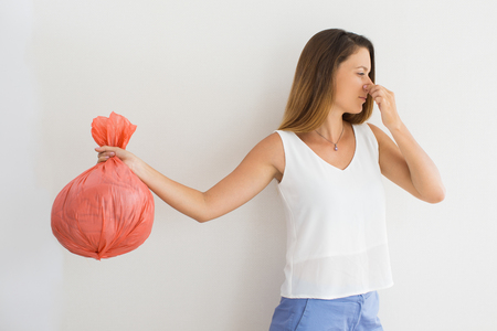 pinched: Displeased woman holding garbage bag Stock Photo