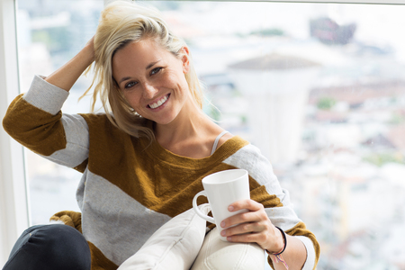 comfortable: Portrait of happy young woman drinking tea at home
