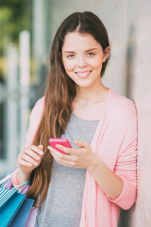 Smiling woman holding shopping bags and smartphone