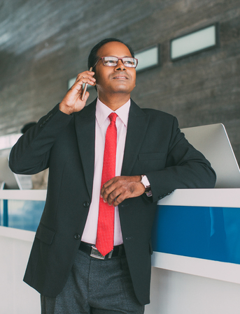 Serious Business Man Calling on Phone at Reception