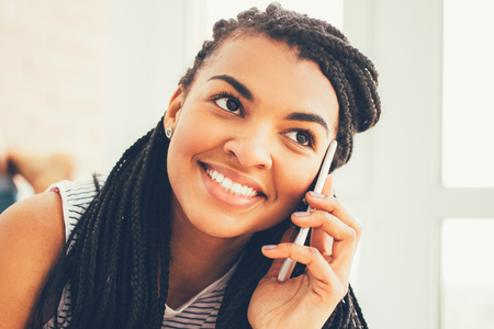 Face of smiling woman answering call on cellphone