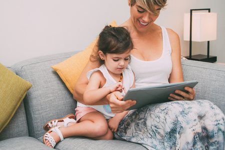 Cheerful mother showing game on tablet to daughter Stock Photo
