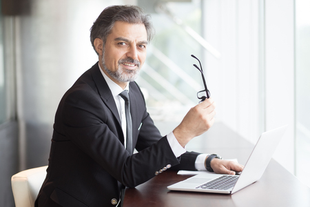 Positive Business Leader Sitting at Office Desk