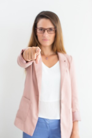 Index finger of businesswoman pointing at camera Stock Photo